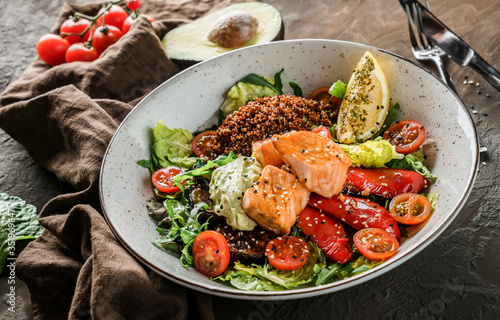 Fototapeta Healthy salad with fillet salmon, quinoa, avocado sauce, grilled pepper, tomatoes, lettuce, arugula in plate on wooden background. Healthy food, clean eating, Buddha bowl, dieting, close up obraz
