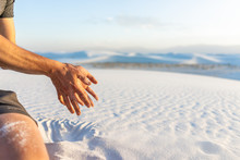 White Sands Dunes National Monument With Man Hand Holding Sand Falling Grains In New Mexico At Sunset