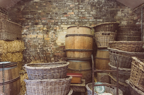Photo Stack Of Wicker Baskets By Barrel Against Wall