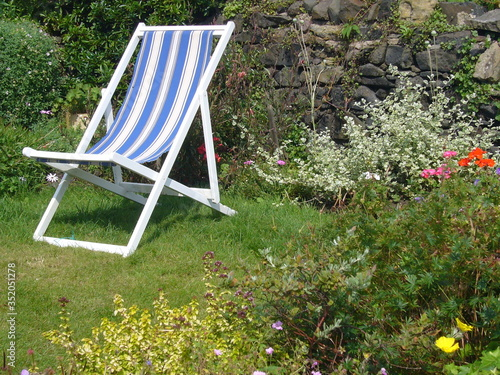 Deck Chair On Grassy Field Against Plants Fototapet