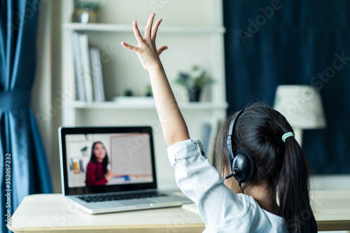 Fotomural Homeschool Asian little young girl student learning virtual internet online class from school teacher by remote meeting due to covid pandemic