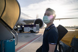 Asian man wearing mask walks into stair entering airplane in airport.