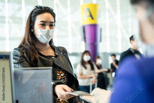 Photo Asian female traveler giving passport to customer check in officer at airline service counter
