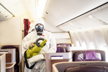 Cleaner officers hold cleaning device on airplane passenger cabin. An employee sprays disinfectant aboard a plane, during airline's sanitary measures to help curb the spread of Coronavirus pandemic.