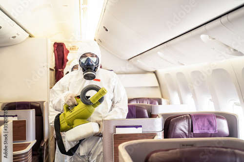 Cleaner officers hold cleaning device on airplane passenger cabin Canvas Print