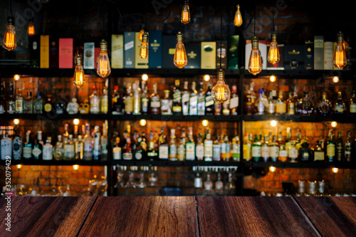 Wooden table with soft liquor bar background Fotobehang