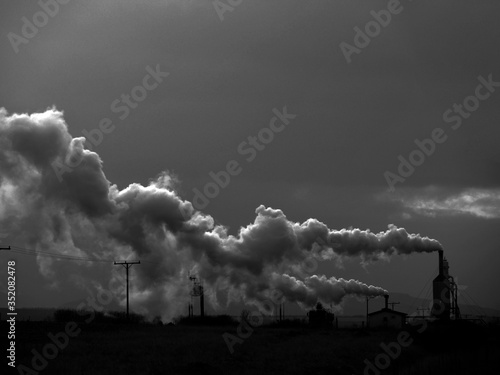 Leinwand Poster Industrial Smoke Stacks Emitting Pollution Against Sky