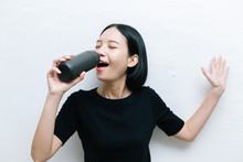 Attractive Asian Female Using A Bottle Of Water To Practice Sing A Song.