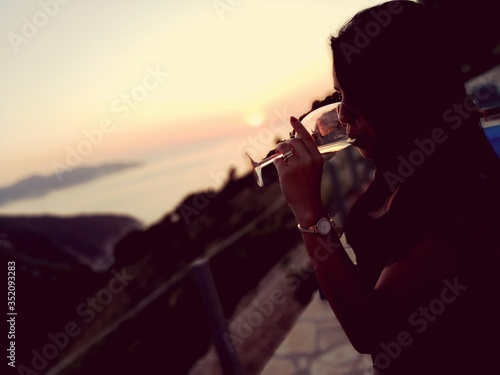 Woman Drinking Wine Against Sea During Sunset Fototapet