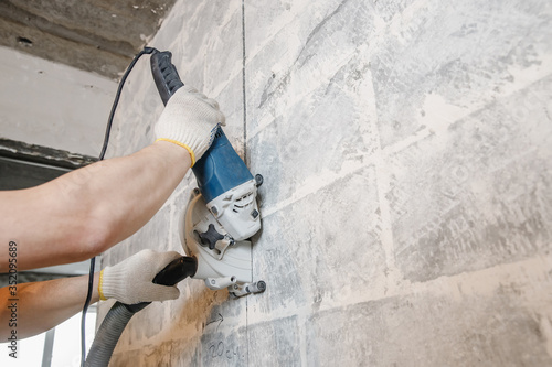 Obraz Builder man cutting electrical chase in concrete wall with circulation saw drill diamond crown - fototapety do salonu