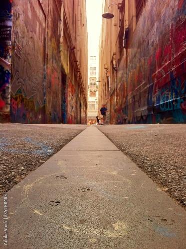 Distant View Of Man Walking On Street Between Buildings With Graffiti Walls © kim dumayne/EyeEm
