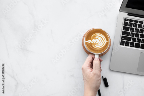 Fotografie, Obraz Hand holding cup of latte coffee over white marble office desk table with laptop computer