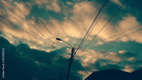Fotografie, Obraz Low Angle View Of Electricity Pylon And Street Light Against Cloudy Sky