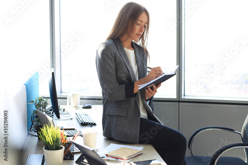 Concentrated young woman writing something down while working in the office Billede på lærred