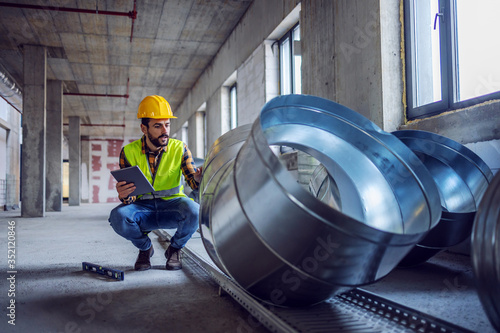 Fotomural Highly motivated caucasian construction worker in work wear crouching next to exhaust pipes and checking on their quality