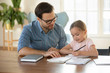 Leinwandbild Motiv Caring young father and little preschooler daughter sit at table at home studying writing in notebook, loving dad or tutor teach small girl child handwriting, learning together, education concept