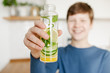 Teenager boy holding glass bottle infused detox water with cucumber, lemon and mint