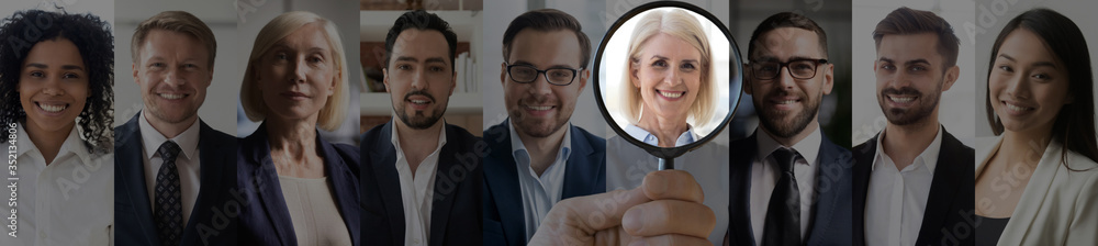Fototapeta Human resource manager hand holding magnifier highlighting choosing old mature female candidate recruit among diverse professional business people faces collage. Horizontal banner for website design.