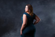 Plus size fashion model in green evening dress, fat woman on black background