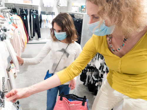 Obraz Mother and daughter in shopping mall with protective medical masks for protection of virus in time of epidemic and pandemic. - fototapety do salonu