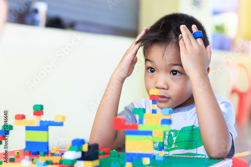 Fototapeta Portrait​ image​ of​ 5-6​ years​ old​ kid.​ Selective​ focus​ of​ Happy​ Asian​ child​ boy​ playing​ with​ the​ plastic​ block​ toys.​ Learning​ and Development​ of​ kid​ concept.​ Study​ at​ home.​ obraz na płótnie