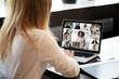 Back view of businesswoman sit at desk have video call with multiracial colleagues on laptop, female employee speak talk on webcam conference on computer, brainstorm with coworkers at meeting online