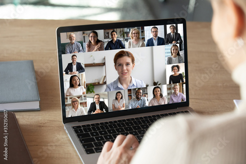 Back view of female employee talk on video call on laptop with diverse colleagues, have group web conference or meeting, woman worker engaged in webcam conversation with coworkers from home - 352150617