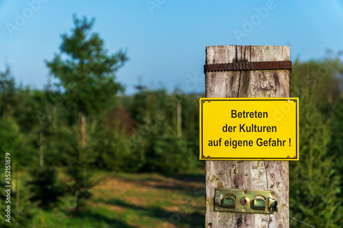 Photo Yellow warning sign with German text Entering the crops at your own risk in front of conifer tree crops on a sunny day in Germany