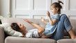 Leinwandbild Motiv Smiling mother playing funny game with little daughter, clapping hands, lying on cozy couch at home, cute preschool girl having fun with loving young mum, family enjoying leisure time together