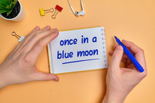 English Idiom Hand Lettering About Time - Once In A Blue Moon On Wooden Blocks.