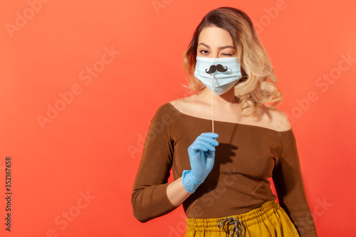 Vászonkép Portrait of positive woman in protective gloves, holding fake mustache accessory over surgical face mask, winking playfully, in good mood in spite coronavirus pandemic threat
