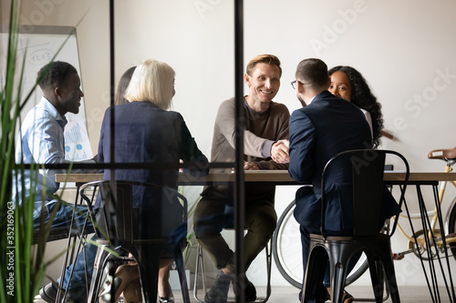 Fototapeta Smiling business partners shaking hands at meeting in boardroom with diverse employees team, making agreement, good legal deal, greeting or introduction, two businessmen handshaking at briefing obraz