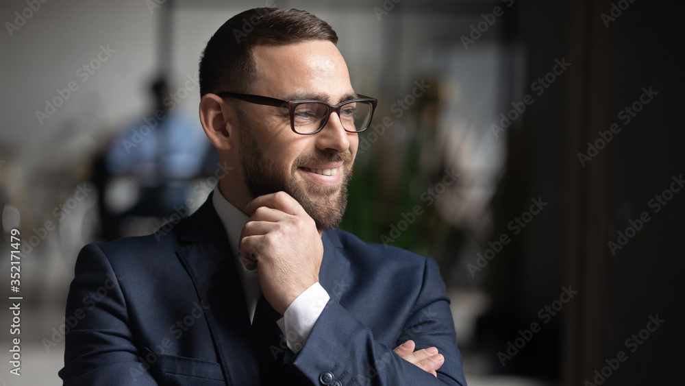 Fototapeta Smiling businessman wearing glasses dreaming about good future close up, touching chin, business vision concept, team leader standing in modern office, looking in distance, thinking about project