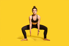 Motivated Athletic Woman With Hair Bun In Tight Sportswear Doing Frog Squat, Lower Body Sport Exercise, Warming Up And Training Muscles For Strength And Flexibility. Full Length Studio Shot, Isolated