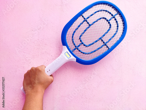 hand is hold Electric mosquito swatter for hit and shock mosquito on pink background Selective focus Tapéta, Fotótapéta