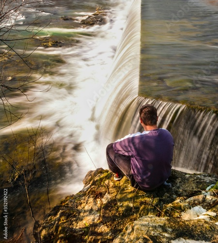 Fototapety, obrazy: Rear View Of Man Sitting By Waterfall