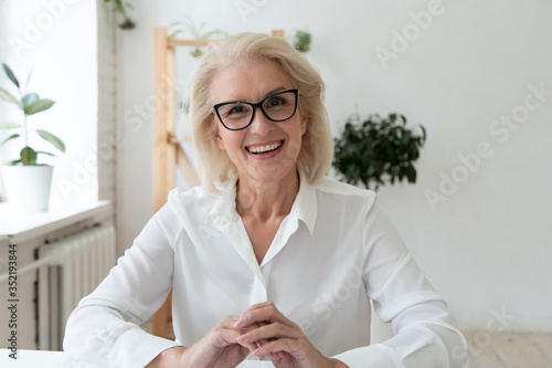Obraz Headshot close up view of smiling middle-aged businesswoman in glasses have video call with business client, happy mature female employee speak talk on WebCam, engaged in web conference in office - fototapety do salonu