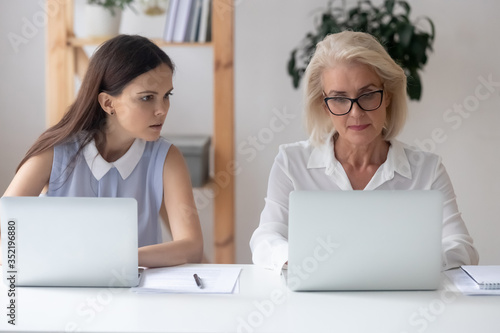 Young female employee look at colleague laptop screen coworking in modern office Fototapet