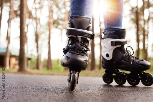 Fotografia Horizontal photo of modern black roller skates being on road outskirts, unknown person riding during weekends, enjoying leisure activities, being fond of active lifestyle