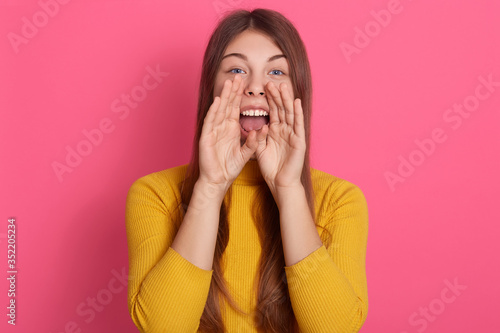 Portrait of energetic loud cute beautiful female opening mouth widely, putting hands to mouth, shouting, making noise, standing isolated over pink background in studio, wearing casual clothes.