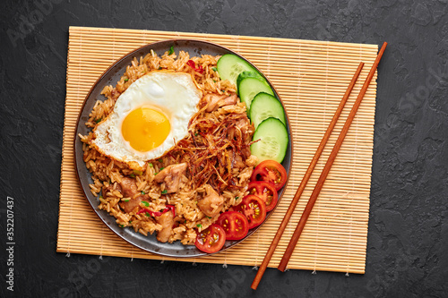 Nasi Goreng - Indonesian Chicken Fried Rice on a black plate on dark slate backdrop Fototapete