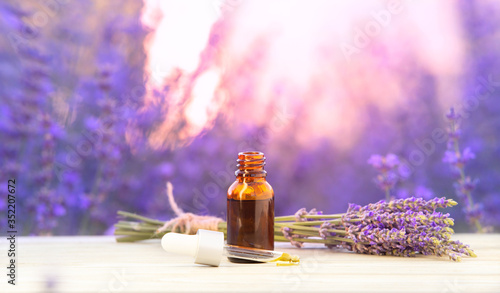 Fototapeta Essential lavender oil in the bottle with dropper isolated on white background. Horizontal close-up. Skincare spa massage. obraz