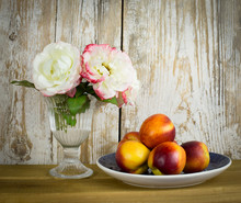 Vintage Still Life With Roses And Peaches On An Old Wooden Background.