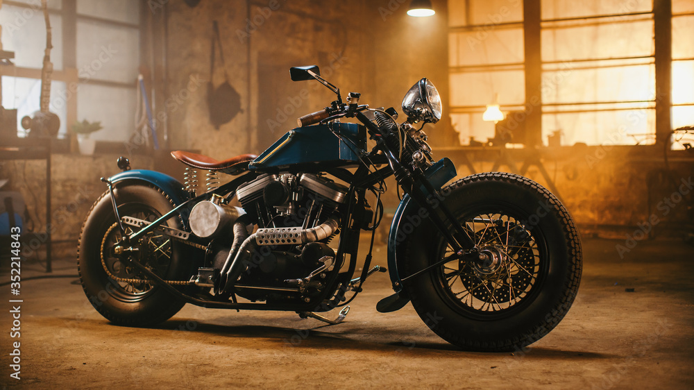 Fototapeta Custom Bobber Motorbike Standing in an Authentic Creative Workshop. Vintage Style Motorcycle Under Warm Lamp Light in a Garage.