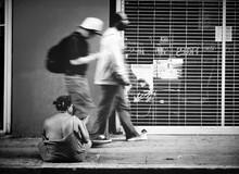 Blurred Motion Of Men Walking By Beggar On Sidewalk