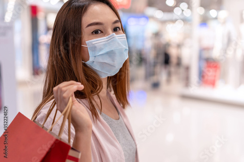Obraz Young asian woman wearing surgical mask shopping in clothes store at the mall, New normal and lifestyle concept - fototapety do salonu