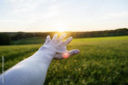 Obraz na plátně Cropped Image Of Hand Gesturing Against Landscape During Sunset