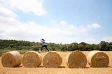 Side View Of Woman Jumping On Hay Bales At Field Against Sky