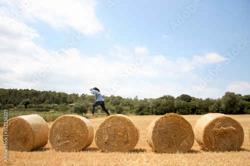 Fotografie, Obraz Side View Of Woman Jumping On Hay Bales At Field Against Sky