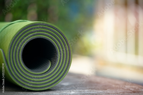 Obraz close up of green yoga mat on the table, sport and healthy concept - fototapety do salonu